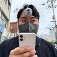 Paeng Min-wook, a postgraduate in innovation design engineering at the Royal College of Art and Imperial College London, showcases a robotic eye, called The Third Eye, on his forehead as he uses his mobile phone while walking on street, in Seoul on March 31. | REUTERS