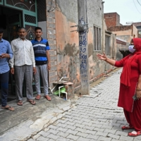 A health worker (right) speaks to a family during a door-to-door COVID-19 vaccine awareness campaign in Kalwa, India, on Tuesday.  | AFP-JIJI