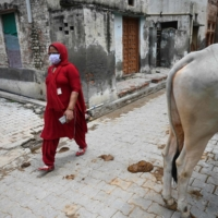 A health worker conducts a door-to-door COVID-19 vaccine awareness campaign on Tuesday in Kalwa, India.  | AFP-JIJI
