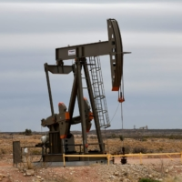 A pump jack operates in front of a drilling rig owned by Exxon near Carlsbad, New Mexico, in February 2019.    REUTERS