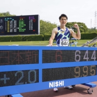 Yamagata poses with a display showing his new national-record 100 time of 9.95 seconds on Sunday at Yamata Sports Park. | KYODO