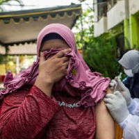 A health worker inoculates a resident with a Sinovac COVID-19 vaccine at a housing complex in Surabaya, Indonesia, on Sunday.    AFP-JIJI