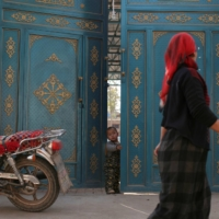 A child looks out from a door as a Uyghur woman walks by in Turpan, in China's Xinjiang Uyghur Autonomous Region, in 2013.  | REUTERS