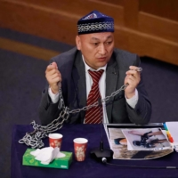 Omir Bekali demonstrates his experience of being shackled, during the tribunal in London on Friday | AFP-JIJI
