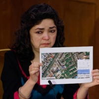 Uyghur teacher Qelbinur Sidik, speaking at the Uyghur Tribunal in London on Friday, holds up a photograph of the hospital where she says she underwent a forced sterilization procedure. | AFP-JIJI