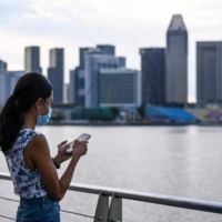 An advertising executive, who wanted to be known as Erica, checks her mobile phone along the Marina Bay promenade in Singapore. Erica is among a growing number of women traveling overseas to get their eggs frozen. | AFP-JIJI