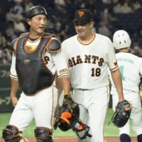 Yomiuri Giants pitcher Tomoyuki Sugano (right) walks off the field with catcher Seiji Kobayashi after the fourth inning against the Hokkaido Nippon Ham Fighters at Tokyo Dome on Sunday.   KYODO