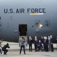 U.S. Sens. Tammy Duckworth, Dan Sullivan and Chris Coons wave next to Taiwan Foreign Minister Joseph Wu and Brent Christensen, director of the American Institute in Taiwan, after their arrival via a U.S. Air Force freighter at Taipei Songshan Airport on Sunday. | CENTRAL NEWS AGENCY / POOL / VIA REUTERS