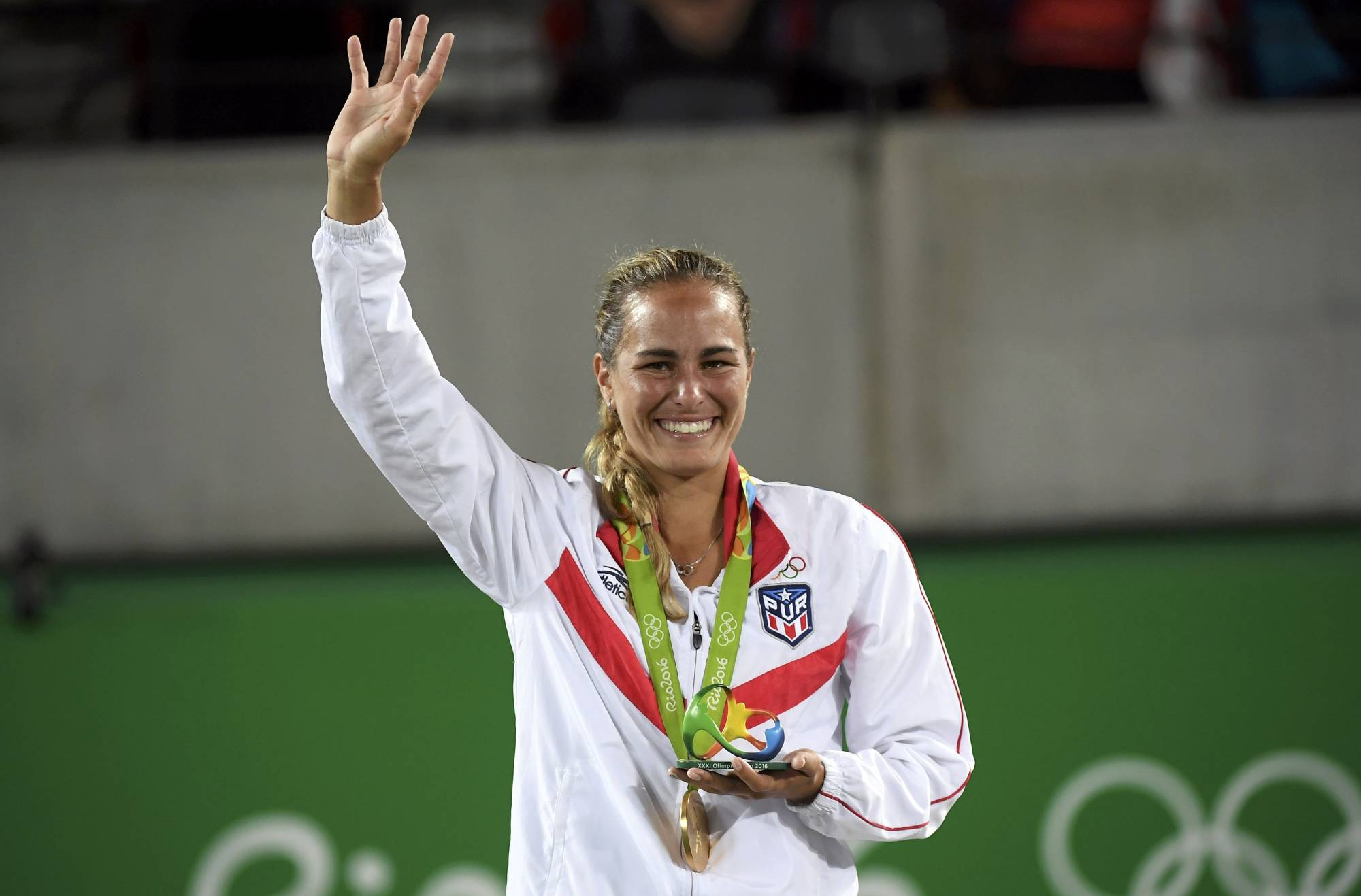 Monica Puig waves during the victory ceremony after winning the women's singles gold medal at the 2016 Rio Games.  | REUTERS