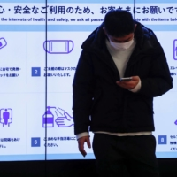 A man wearing a protective face mask stands in front of an electric screen displaying initiatives to prevent COVID-19 infections in the arrival zone of the international flight terminal at Tokyo's Haneda Airport last December. | REUTERS