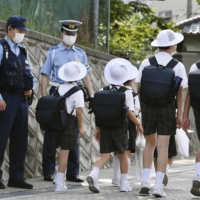 Students head to Ikeda Elementary School in Osaka Prefecture as police officers stand by.   KYODO