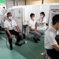 Firefighters receive their first dose of COVID-19 vaccines at a mass vaccination site opened Tuesday at the former Tsukiji fish market in Tokyo. | AFP-JIJI