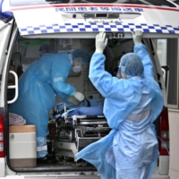 Emergency medical staff leave a hospital after transporting a COVID-19 patient in Sakai, Osaka Prefecture, last month. | KYODO