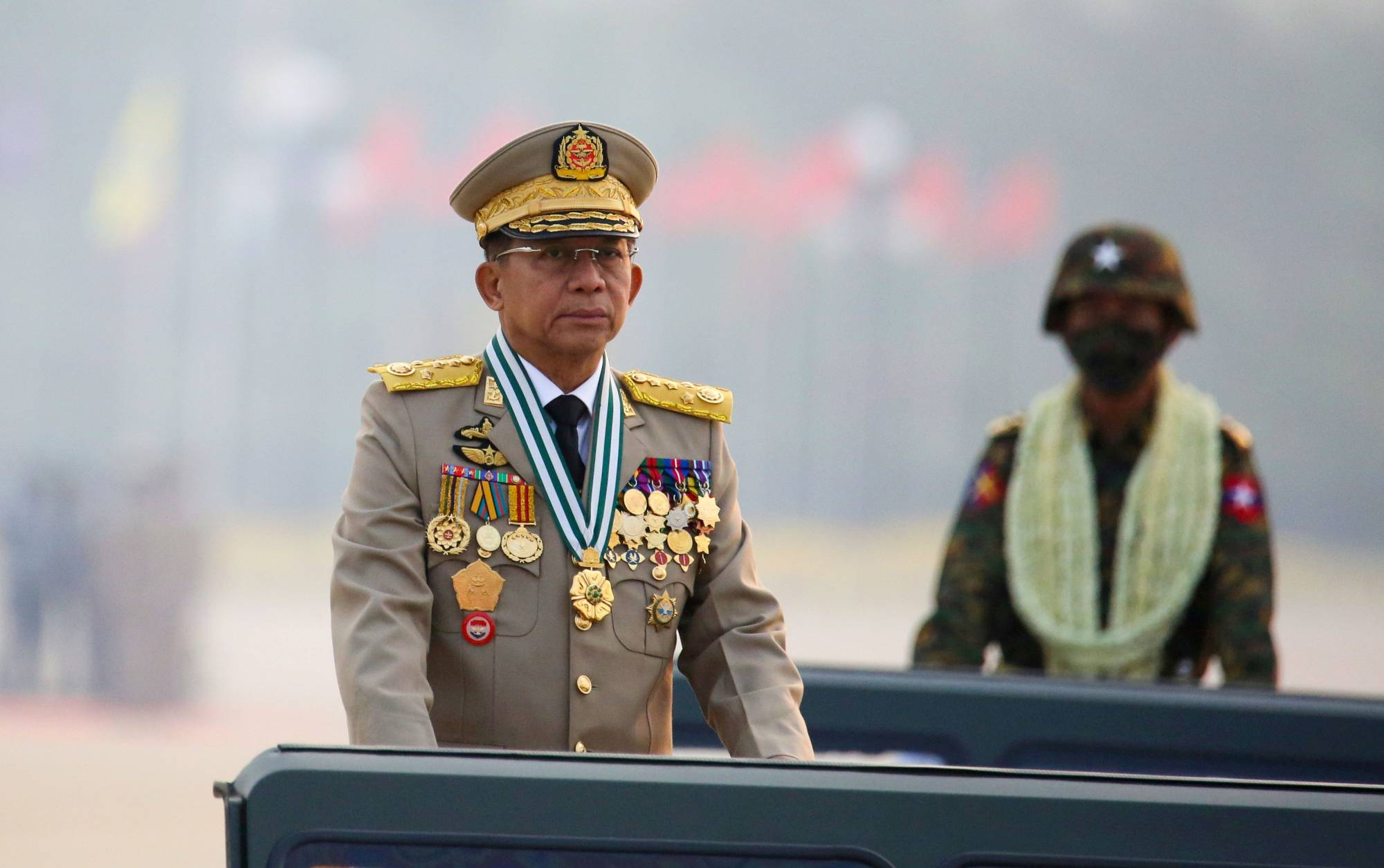 Myanmar's junta chief Gen. Min Aung Hlaing, who ousted the elected government in a coup on Feb. 1, presides over an army parade on Armed Forces Day in Naypyitaw, Myanmar, in March.  | REUTERS
