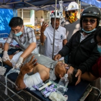 A protester, injured after being shot at with live rounds, gives a three-finger salute while receiving treatment at a makeshift medical center in Mandalay, Myanmar, in February. | AFP-JIJI