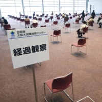 People observe their condition after being given a coronavirus vaccine at the mass inoculation center run by the Self-Defense Forces in Osaka on Wednesday.   POOL / VIA KYODO