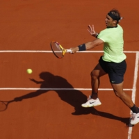 Rafael Nadal hits a return during his quarterfinal match against Diego Schwartzman at the French Open in Paris on Wednesday. | REUTERS
