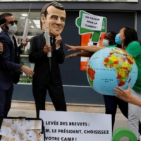 An Oxfam activist wearing a giant head depicting French President Emmanuel Macron protests ahead of the G7 leaders' summit against patents on COVID-19 vaccines, in Paris on Tuesday.    | REUTERS