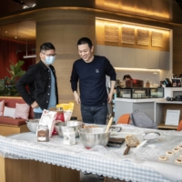 William Li speaks with a customer during a cooking demonstration at a Nio House in Shanghai in March.  | BLOOMBERG