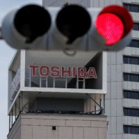 """Four Toshiba Corp. directors called on Friday for a shake-up of its management and board, in a sign of revolt after an investigation found the conglomerate colluded with the Japanese government to """"beat up"""" foreign shareholders."""
