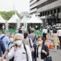 Older people outside a large-scale state-run COVID-19 vaccination center in Tokyo last week. | KYODO