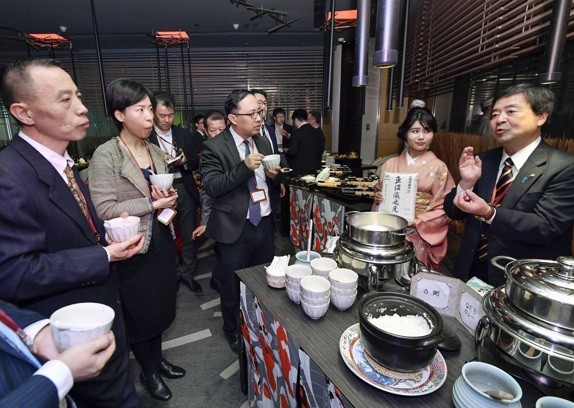 Haruyuki Yamada (right), Niigata Prefecture's agriculture affairs division chief, introduces locally made rice during an event to promote the product in November 2019 in Beijing. | KYODO