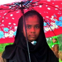 A Rohingya refugee holds an umbrella after she and a group arrived in Pulau Idaman, a small island off the coast of East Aceh in northern Sumatra, on June 4. | AFP-JIJI
