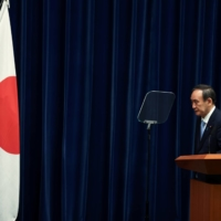 Prime Minister Yoshihide Suga bows in front of the national flag at a news conference after announcing the government's decision to extend a COVID-19 state of emergency, at the Prime Minister's Office in Tokyo on May 28. | REUTERS