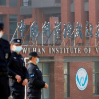 Security personnel keep watch outside the Wuhan Institute of Virology during a visit by the World Health Organization team tasked with investigating the origins of the coronavirus, in Wuhan, China, on Feb. 3. | REUTERS