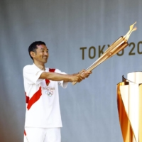 Former Olympic sprinter Dai Tamesue participates in the lighting of the Olympic cauldron in Fukuyama, Hiroshima Prefecture, on May 18. | KYODO