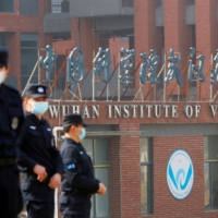 Security personnel keep watch outside Wuhan Institute of Virology during the visit by the World Health Organization team tasked with investigating the origins of COVID-19, in Wuhan, China, on Feb. 3. | REUTERS