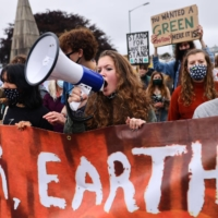 A woman holds a megaphone during a climate protest in Falmouth, England, on Friday. | REUTERS