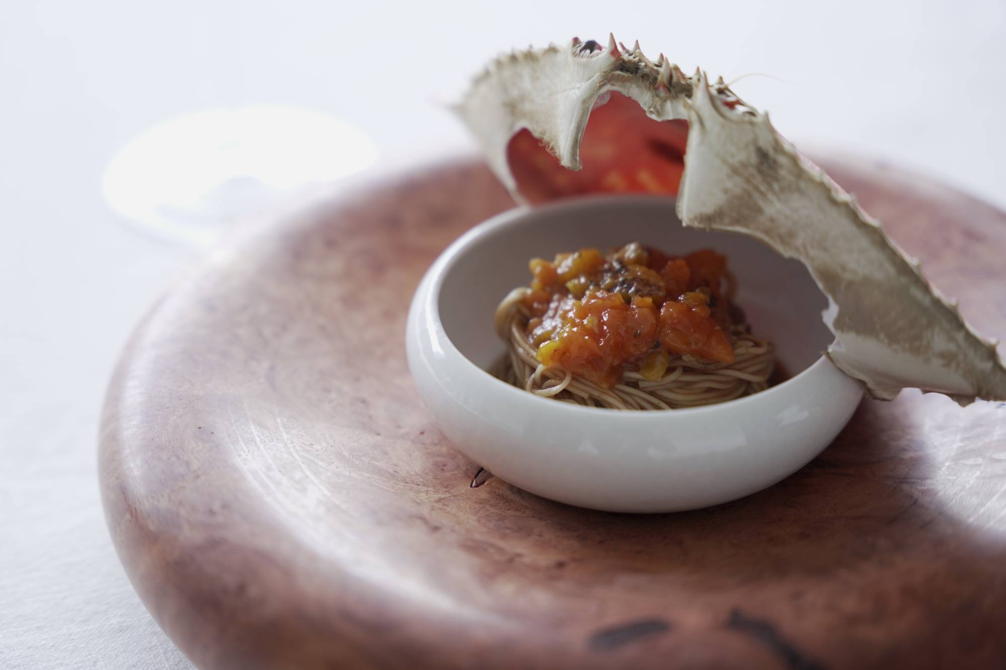 Tenobe sōmen wheat noodles dunked into a dark, savory sauce of crab innards, twisted tightly and served with chunks of crab meat. | NAOH INC.