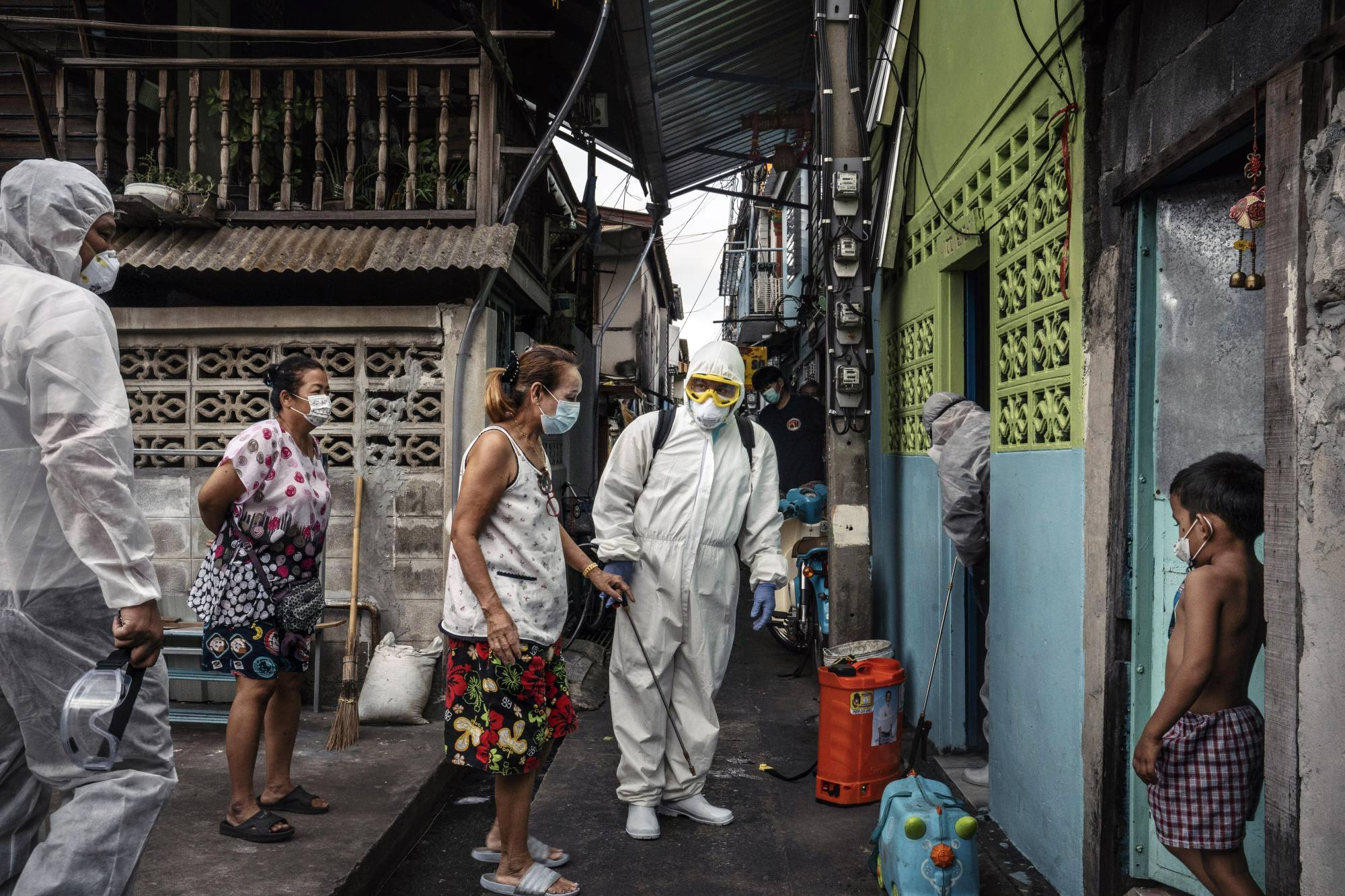 Workers prepare to spray disinfectant in homes where people tested positive for COVID-19 in Bangkok on May 7. All across the Asia-Pacific region, the countries that led the world in containing the coronavirus are now languishing in the race to put it behind them. | ADAM DEAN / THE NEW YORK TIMES