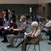 People wait for a medical consultation prior to receive a dose of the Pfizer-BioNTech COVID-19 vaccine at an inoculation site at Miyakojima Sports Center in Osaka on June 1.  | BLOOMBERG