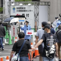 People walk to a mass COVID-19 vaccination center in Tokyo's Otemachi district on Monday. | KYODO