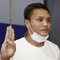 Pyae Lyan Aung, a substitute goalkeeper for the Myanmar national team, raises a three-finger salute in protest against the coup at Kansai International Airport in Osaka Prefecture early Thursday after refusing to fly back home.   KYODO