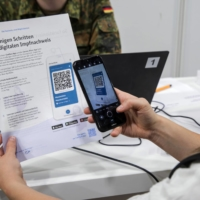 A visitor uses CovPass, Germany's new vaccination passport smartphone app, to scan a QR code after being inoculated at a COVID-19 vaccination center in Berlin earlier this month.  | BLOOMBERG