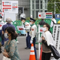 People age 18 and older go to the mass vaccination center run by the Self-Defense Forces in Tokyo on Thursday. | KYODO