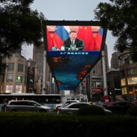 A large screen outside a shopping mall in Beijing shows a news report about Chinese President Xi Jinping on May 19. | AFP-JIJI