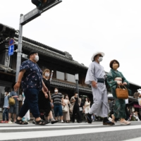 Pedestrians cross a street in the warehouse district of Kawagoe, Saitama Prefecture, on Sunday. Consumer prices rose slightly in May, showing a year-on-year increase for the first time in 14 months. | BLOOMBERG