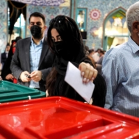 A woman casts her ballot at a polling station in Tehran on Friday during Iran's presidential election.    AFP-JIJI