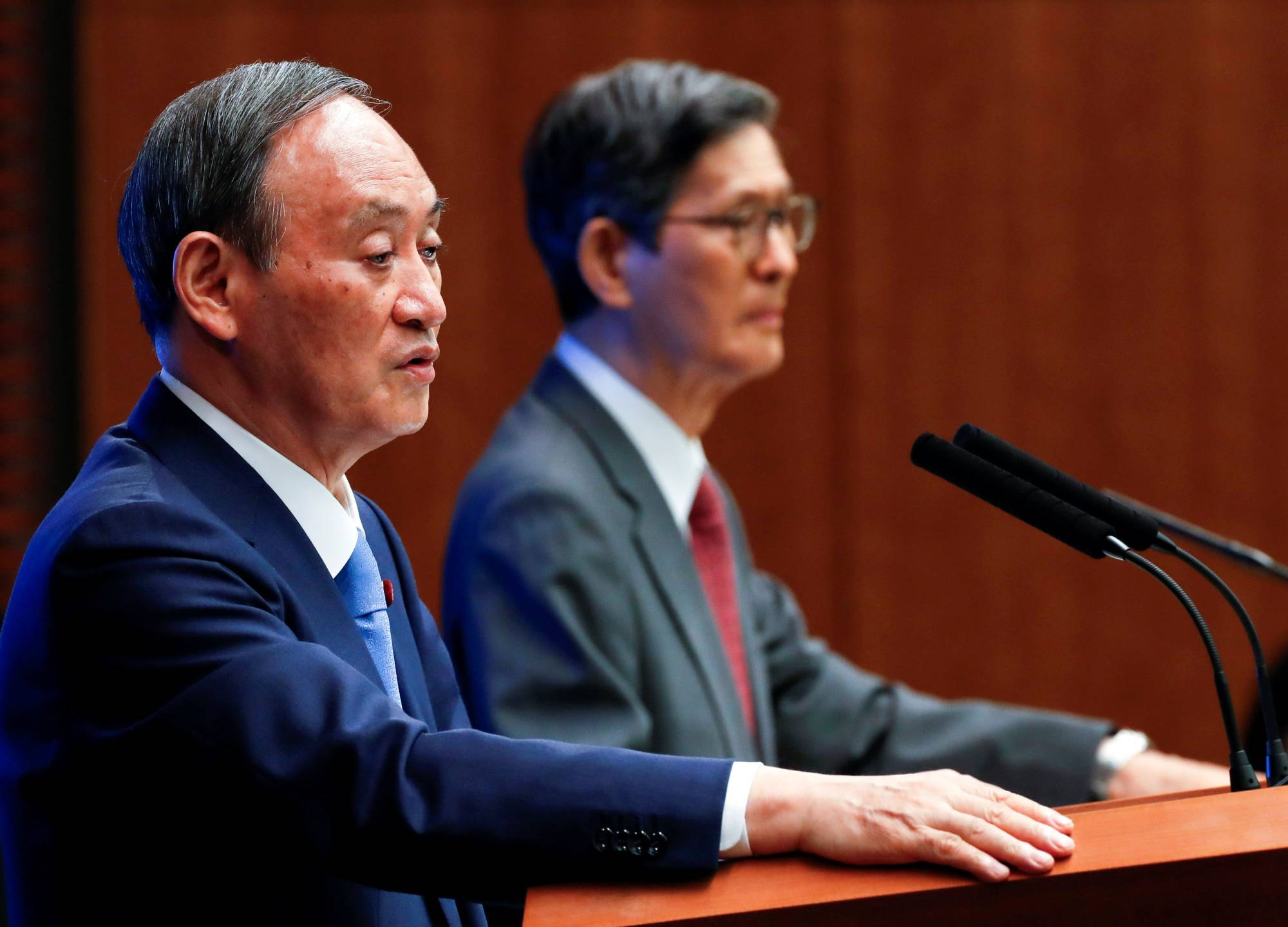 Prime Minister Yoshihide Suga and Shigeru Omi, chairman of the government's pandemic advisory panel, hold a news conference in Tokyo on Thursday. | POOL / VIA REUTERS
