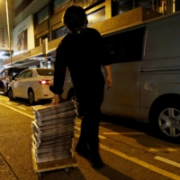 A supporter of the Apple Daily newspaper wheels a stack of the paper's Friday edition. | REUTERS