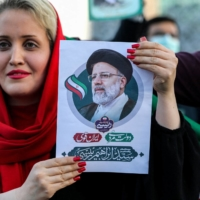 A woman holds a picture of Iran's newly elected president, Ebrahim Raisi, as supporters celebrate his victory in Imam Hussein square in Tehran on Saturday.    AFP-JIJI