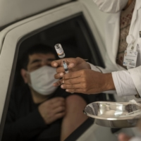 A health worker prepares a dose of the Sinovac Biotech COVID-19 vaccine in Sao Paulo on Friday. Many Brazilians are shunning two of the most widely available vaccines in the country and waiting it out for Pfizer shots.  | BLOOMBERG