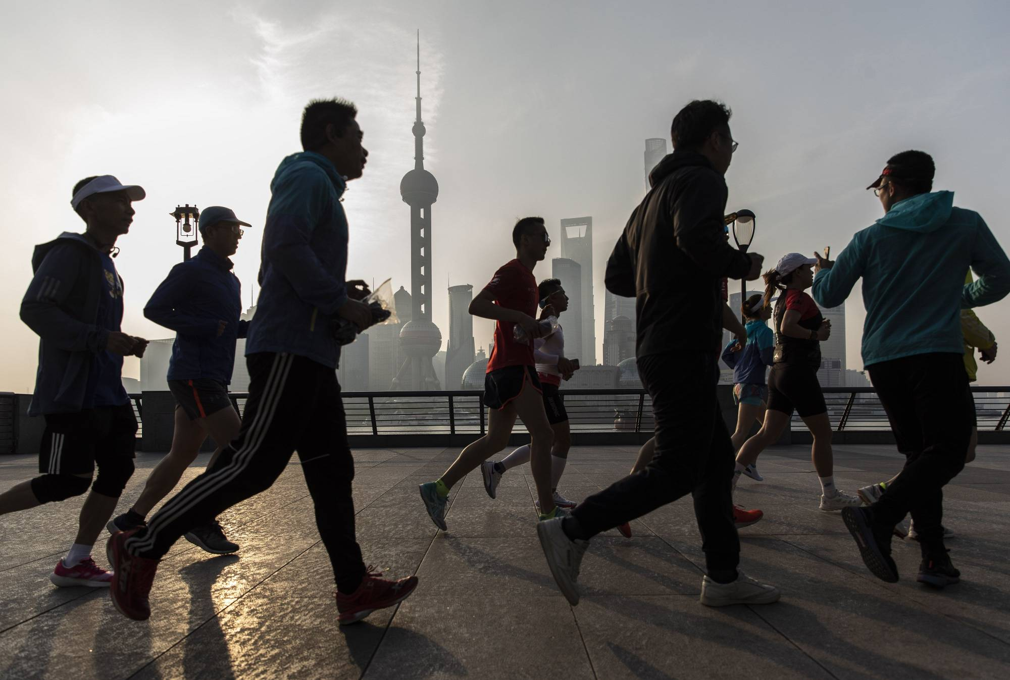Joggers run along the Bund, with Shanghai's Lujiazui Financial District in the background.    BLOOMBERG