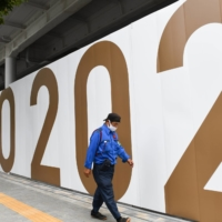A worker walks past the National Stadium, the main venue for the Tokyo Olympics and Paralympics, in Tokyo on Friday. | BLOOMBERG