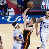 Hawks guard Kevin Huerter scores while being guarded by the Sixers' Seth Curry during the fourth quarter in Philadelphia on Sunday. | USA TODAY / VIA REUTERS