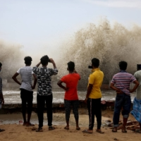 People take pictures of waves breaking on a beach front in Digha following Cyclone Yaas. | REUTERS